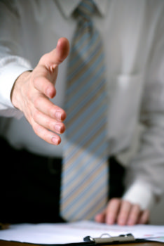 This photo shows a man leaning over a desk to shake hands. This job seekers is being welcomed to their new job after following this article's advice